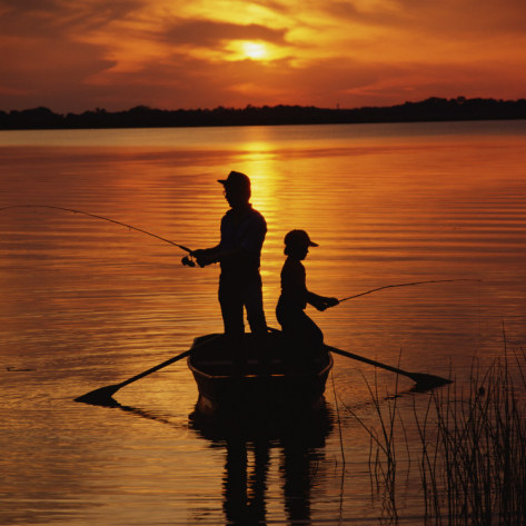 dennis-hallinan-silhouette-of-father-and-son-fishing-at-sunset in boat